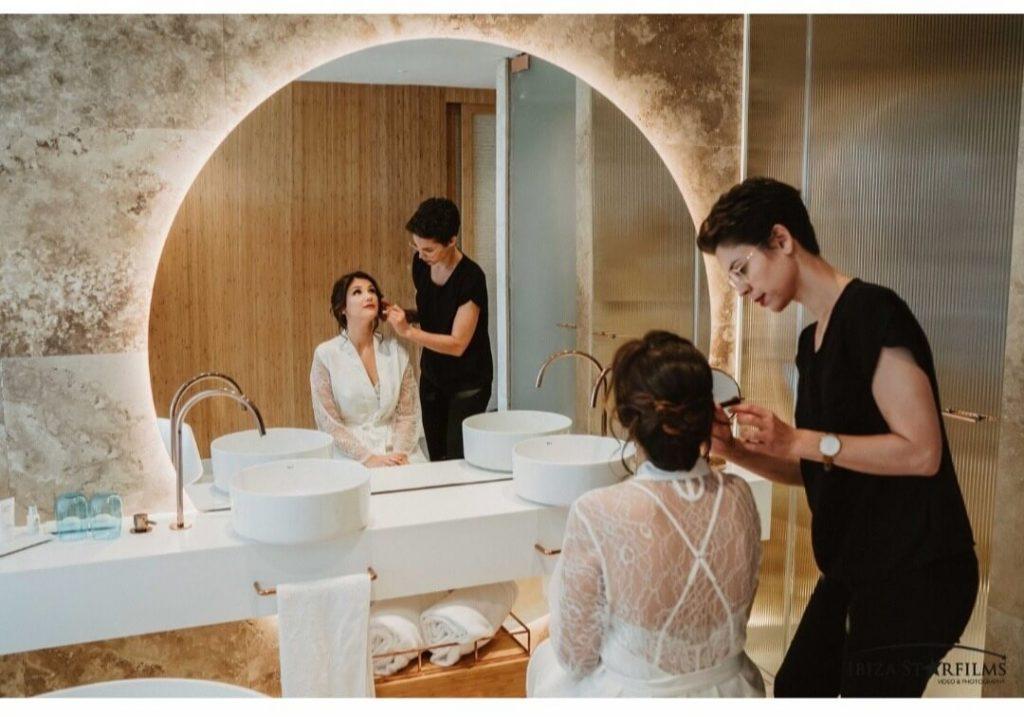 Sandra retocando a una novia mientras realiza el servicio de maquillaje a domicilio en Ibiza